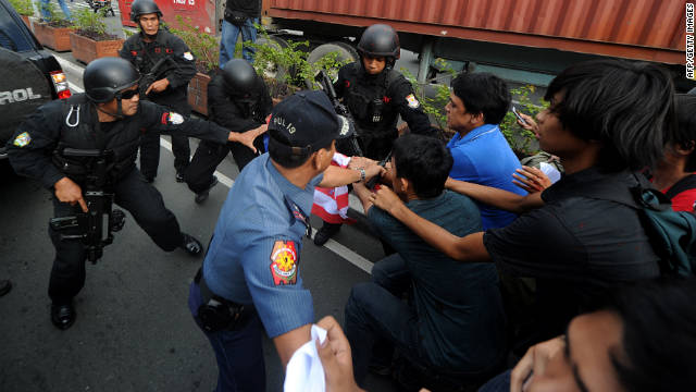 Police clash with Philippine protesters Wednesday as they block the path of Secretary of State Hillary Clinton's motorcade.