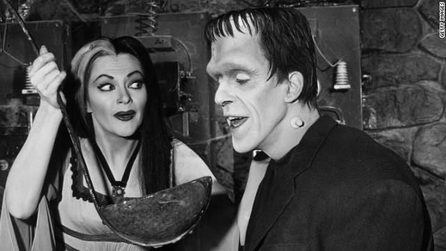 "Lily Munster (Yvonne De Carlo) holds a giant ladle for Herman Munster (Fred Gwynne) in an episode of ""The Munsters."""