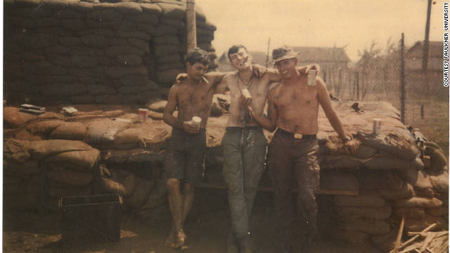 Moore, seen here with friends in Vietnam, had hoped to avoid combat duty by volunteering for the military.