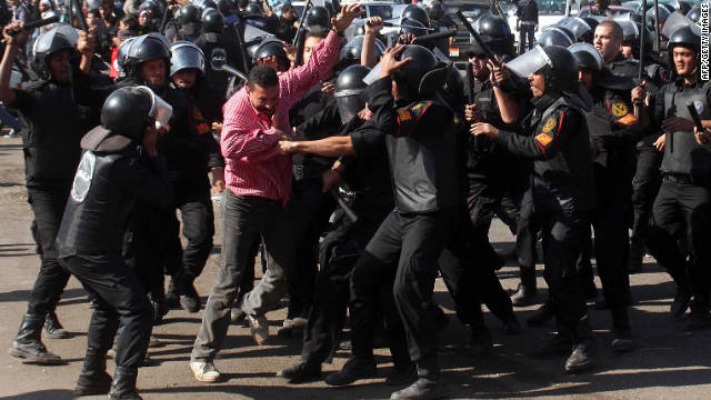 Egyptian riot policemen scuffle with a protester at Cairo's Tahrir Square on Saturday
