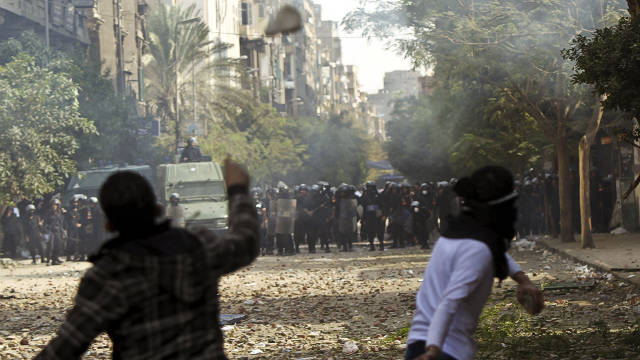 Egyptian protesters throw stones at riot police in Cairo's Tahrir Square on Sunday.