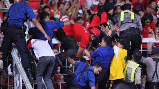 Indonesian security officials evacuate Indonesian football supporters during the final match at the Southeast Asian Games.