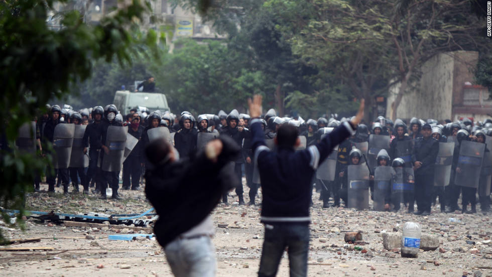 Egyptian protesters hurl rocks at riot police Sunday in Tahrir Square.
