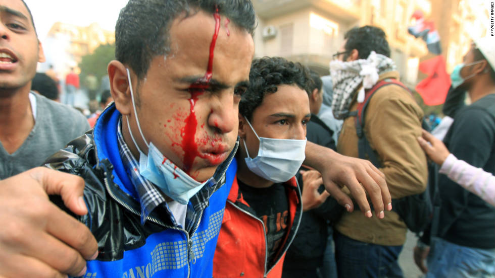 A protester bleeds as he is helped away from fighting Monday in Tahrir Square.