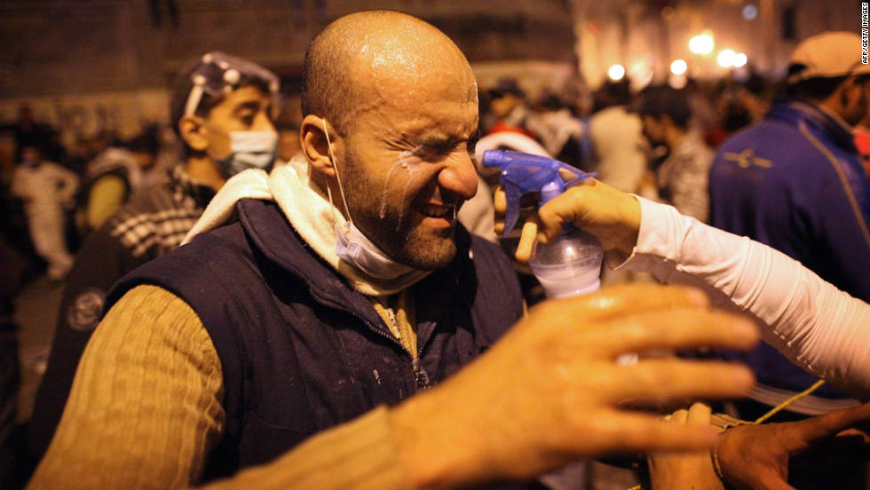 A protestor has his eyes sprayed to help counteract the effects of tear gas near Tahrir Square on November 22, 2011 in Cairo.
