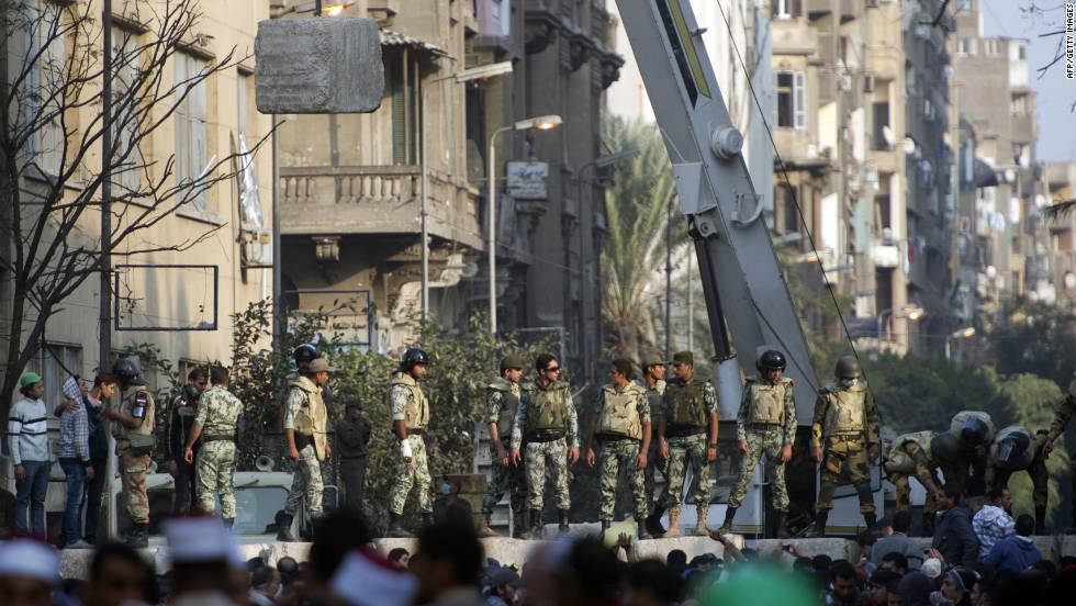 Egyptian military personnel construct a concrete barrier Thursday near Tahrir Square to separate police and protesters.