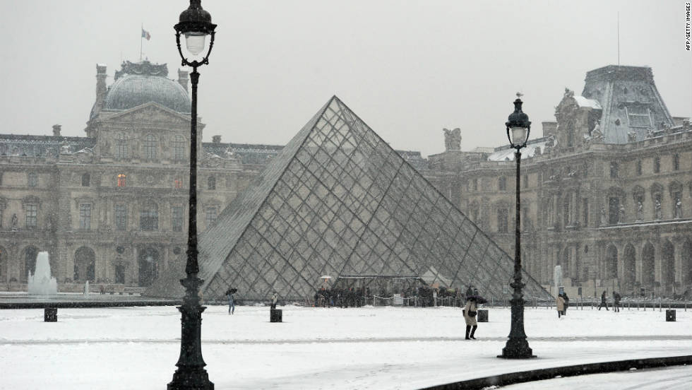 Few tourists are in sight as snow blankets the Louvre Museum.