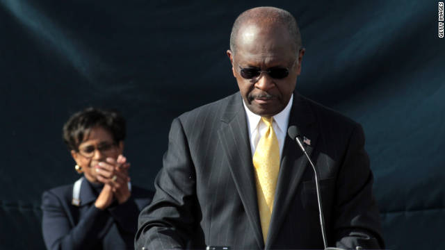 Herman Cain announces that he is suspending his campaign as as his wife, Gloria Cain, looks on.