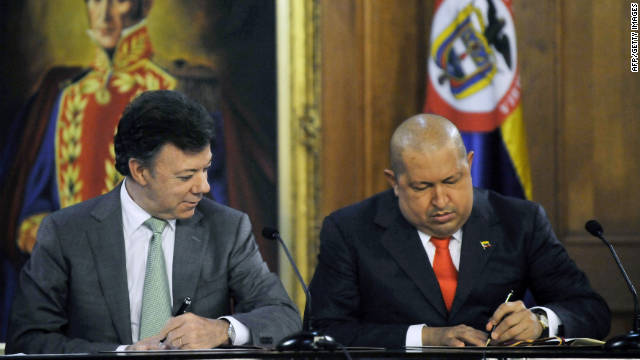 Venezuelan President Hugo Chavez, right and Colombian counterpart Juan Manuel Santos sign bilateral agreements in Caracas.
