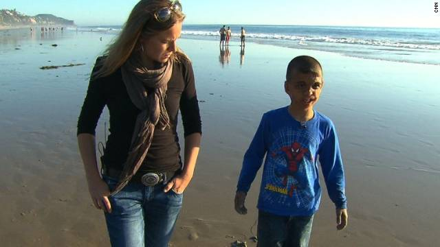 Youssif walks along the California beach with CNN's Arwa Damon, who first told the boy's story in 2007.