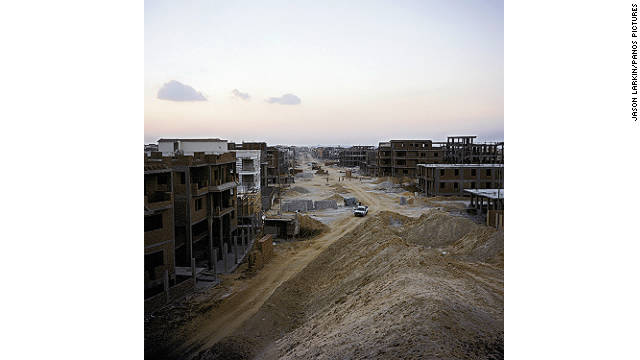 A street of individually owned villas and apartment blocks rises from the sand in New Cairo, one of the new satellite 'ghost towns.'