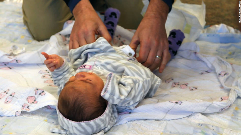 A father-to-be learns how to change a diaper during the daddy boot camp workshop.