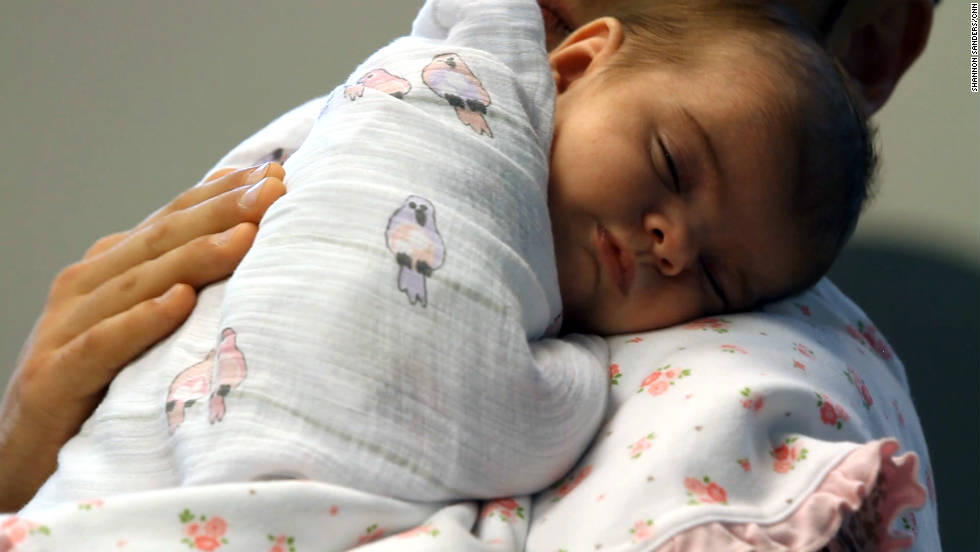 A daddy boot camp participant holds Anabella as she falls asleep.