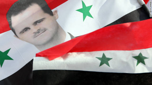 A portrait of Syrian President Bashar al-Assad is seen on a flag carried by supporters during a rally in Damascus, Syria.