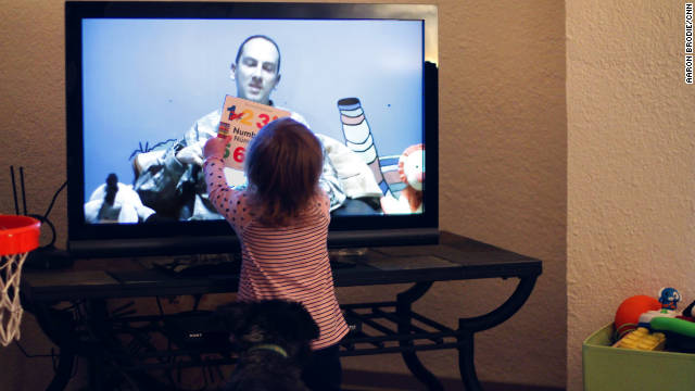 Harper holds a book up to the TV as she and her mother, Alexandra, Skype with her father, in November.