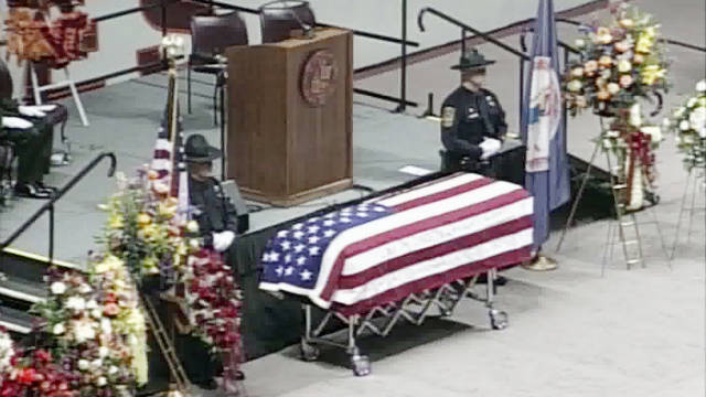Police officers stand guard Monday over the casket of Deriek Crouse, the Virginia Tech officer who was shot to death last week.