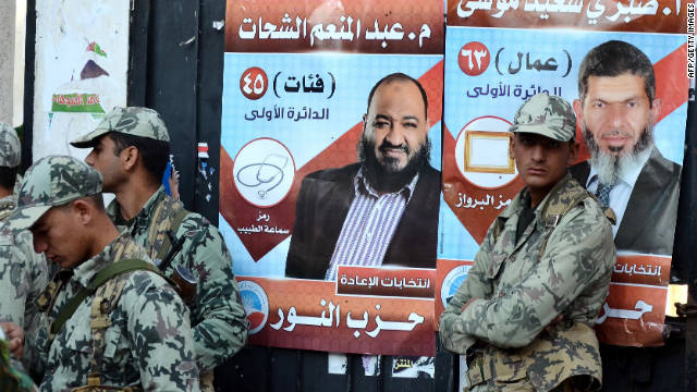 Egyptian soldiers stand in front of  posters for hardline Islamists. Khaled Elgindy thinks the Army is the real threat to reform.