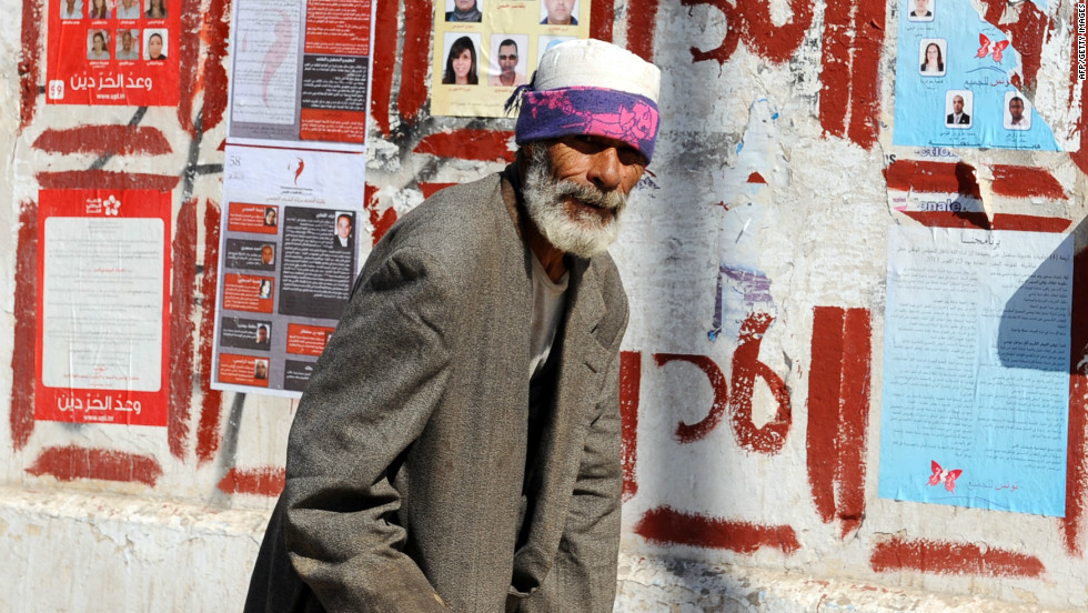 A beggar walks past election posters on October 19, 2011 in Tunis. Tunisians swore in a new president, secularist former human rights activist Moncef Marzouki on December 13.