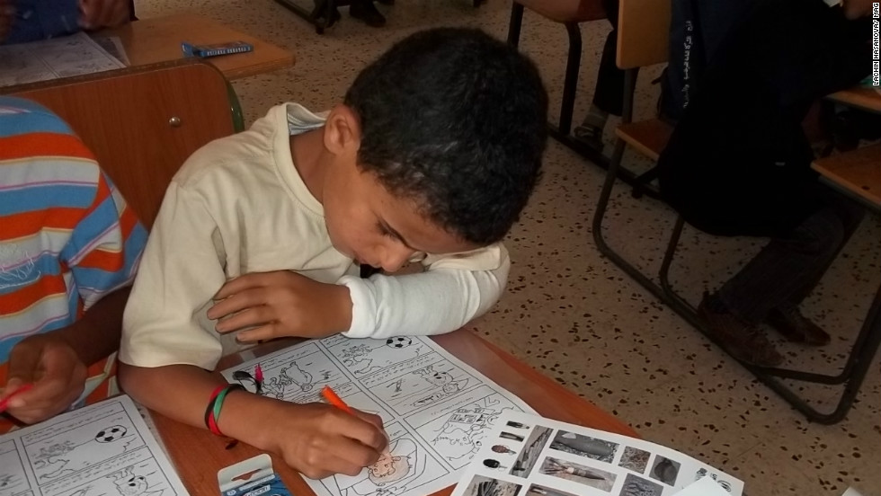 Mahmood with his new plastic hand, does coloring during a Risk Education session run by Mines Advisory Group.