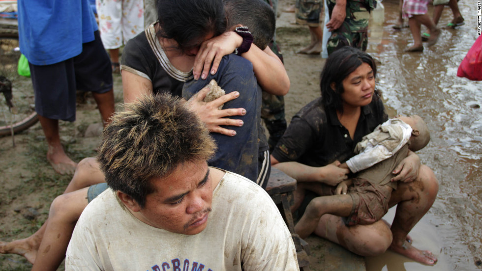 Two mothers hold the bodies of their children Saturday at a village in Iligan City.