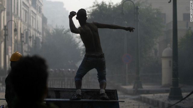 An Egyptian protester against continuing military rule throws stones at riot policemen during clashes in central Cairo Saturday.