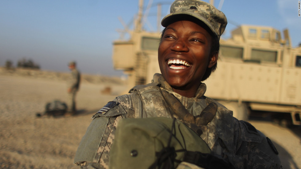 Specialist Shunterika Lewis from the 3rd Brigade, 1st Cavalry Division laughs while preparing to depart in the last convoy from Iraq at Camp Adder.