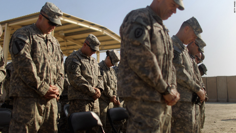 Soldiers from the 3rd Brigade, 1st Cavalry Division bow their heads in prayer during a casing of the colors ceremony while preparing to depart from Iraq at Camp Adder, now known as Imam Ali Base, near Nasiriyah, Iraq.