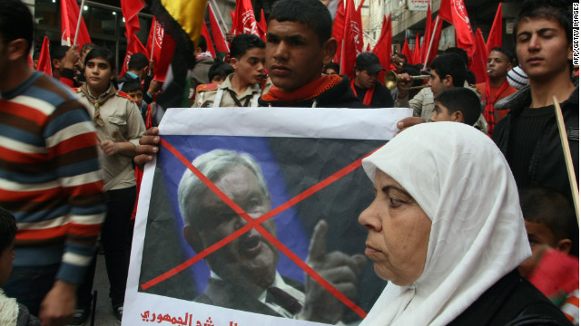 "Palestinians at a West Bank protest hold a crossed-out picture of GOP candidate Newt Gingrich after his comment that Palestinians were ""an invented"" people."