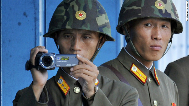 North Korean soldiers look and film footage of the south side of the demilitarized zone in September 2011.