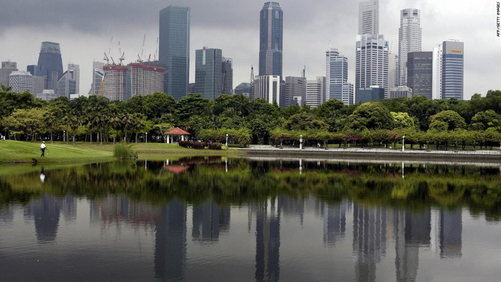 A crowded row of skyscrapers are reflected on a man-made lake while a dark cloud hovers in Singapore. Matthew Kahn, economics professor at the UCLA's Environment Institute, says that this type of high-rise, high-density urban living will be the norm in years to come, as cities adapt to migrants escaping their climate-ravaged homes.