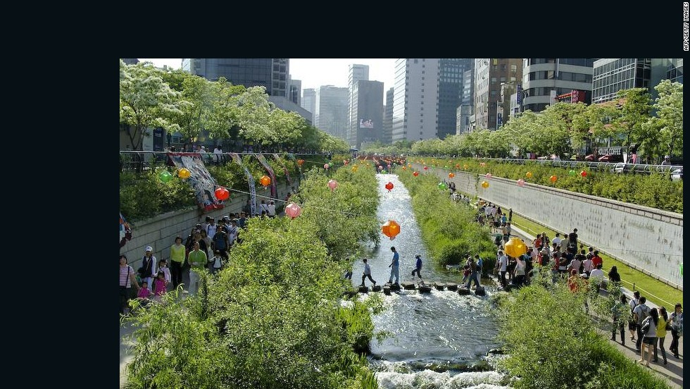 """A newly restored stream flows through high-rise buildings in the center of Seoul in September 2005. The city revived the 5.8 kilometer (3.5 mile) stretch of the stream, which was buried under concrete for decades during South Korea's headlong scramble for economic development. Simon Reddy from the C40 Cities network says the river will help create a """"wind corridor"""" to keep the city cool as temperatures rise."""
