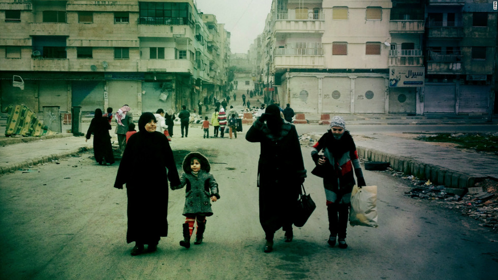 Despite the threat from snipers, a family makes its way down Cairo Street in Al Khaledia in Homs, Syria.