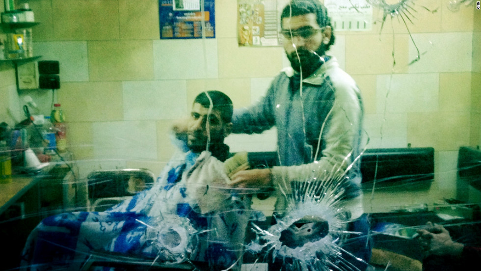 A barber stares through his bullet-marked window in the center of Baba Amr.