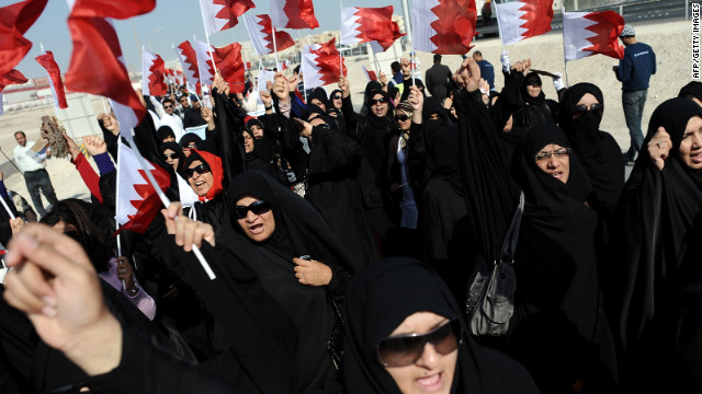 Women in Isa Town wave the Bahraini flag on Tuesday during a rally of Shiite workers who lost their jobs for protesting.