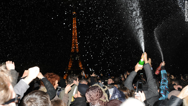 People spray champagne as they celebrate the New Year on the Trocadero square in front of the Eiffel Tower in Paris early on January 1, 2012.