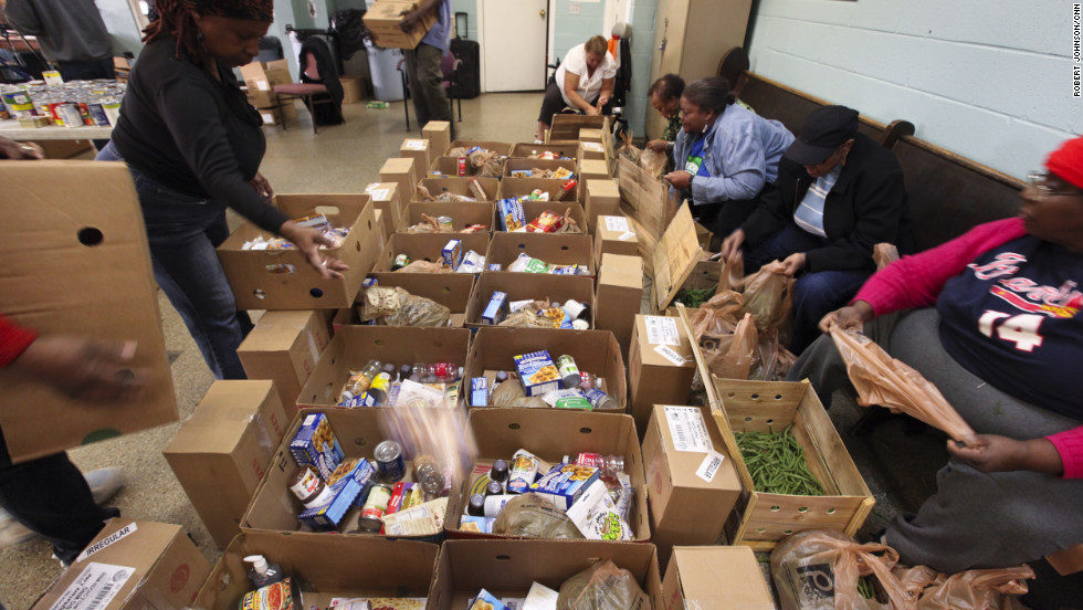 Members pack boxes with a hodgepodge of items ranging from cereal and canned goods to cleaning supplies.