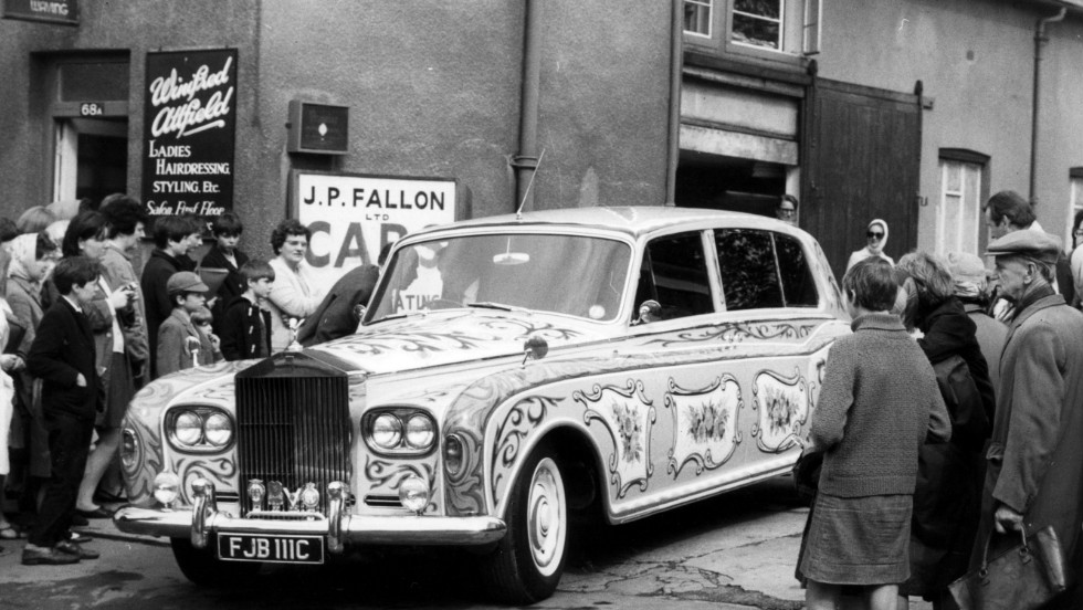 Two years on and psychedelia has taken hold. Here a crowd gathers to watch as John Lennon's Phantom V leaves the coachbuilders after its paint job. Rolls-Royce was reported to have disapproved of the color scheme.