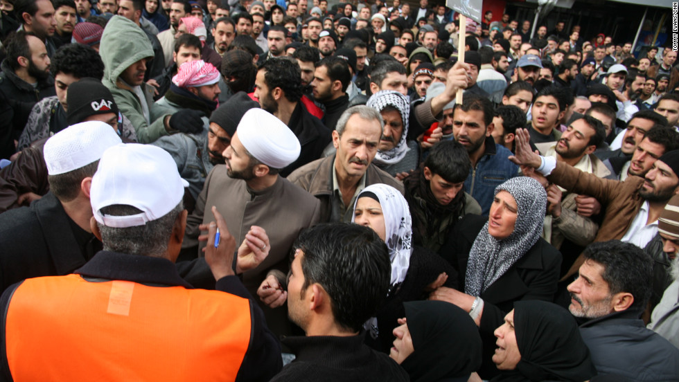 A crowd forms around Arab League observers as they speak to the local imam, a religious leader.