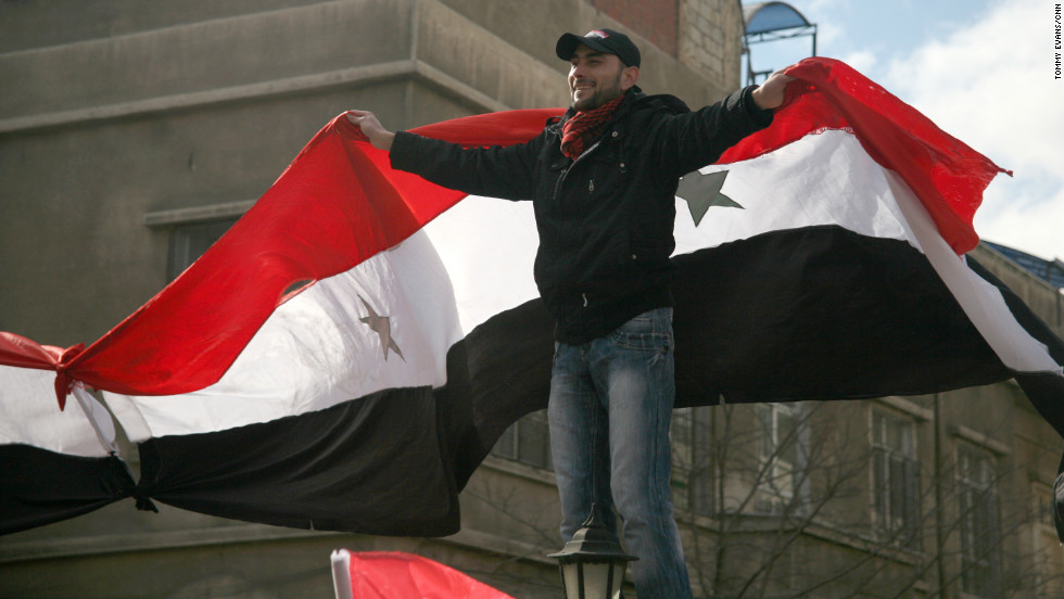 An al-Assad supporter climbs a wall to display a Syrian flag.