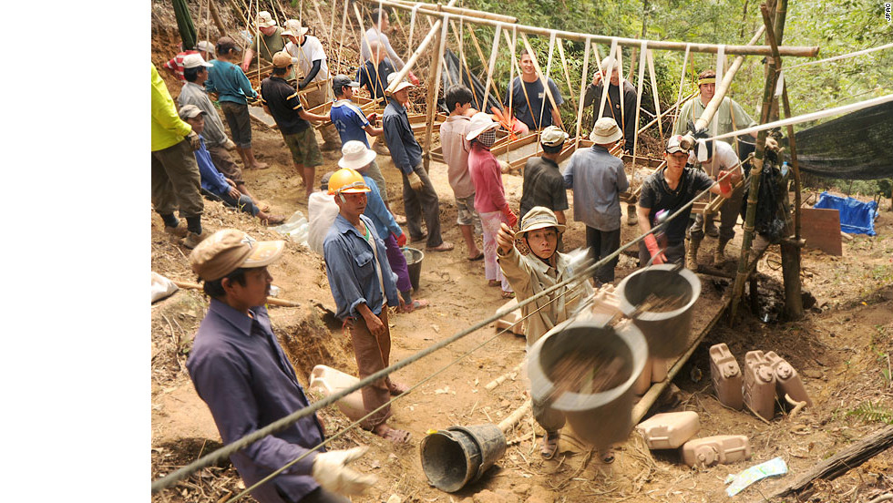 Vietnamese workers use a zip line to move dirt from a dig site to a screening area in the Thua Thien-Hue province, Vietnam.