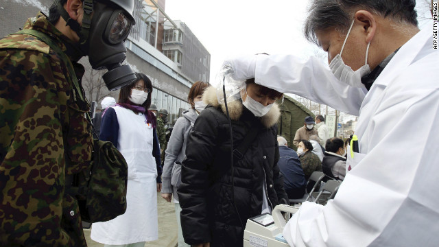 A doctor checks the level of radiation on a woman at a treatment centre in Nihonmatsu city on March 13, 2011.
