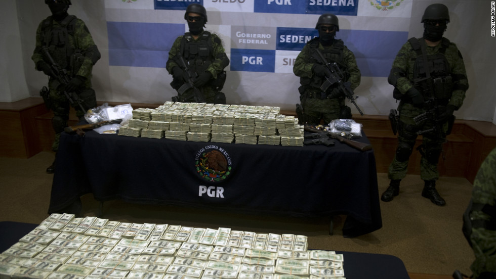 Mexican army soldiers display $15 million U.S. on November 22, 2011, in Mexico City. The money was seized from alleged members of the Guzman Loera drug cartel during a raid in the border town of Tijuana, Mexico.