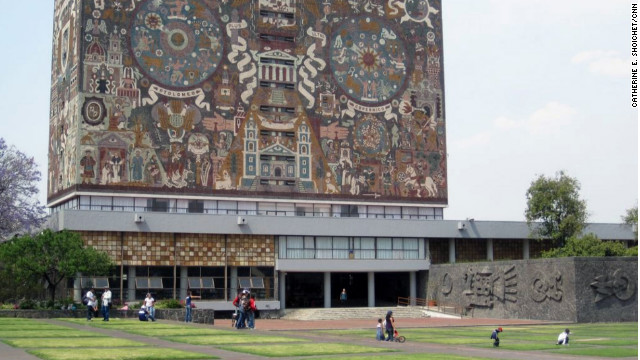 Students and families lounge on the grass outside the Central Library at the National Autonomous University of Mexico.