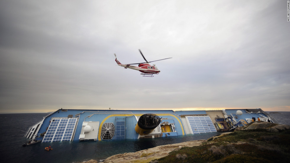 Firemen search for missing people in and around the partially submerged Costa Concordia cruise ship on January 16.