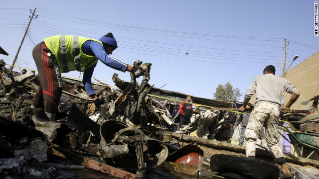 Iraqi men check the debris after a suicide bomber targeted a funeral procession in Baghdad Friday.