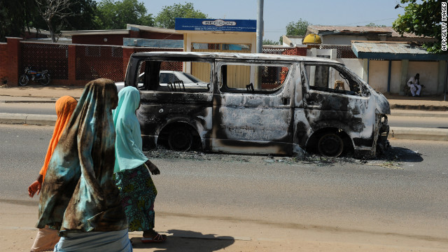 Young Nigerian girls walk past a vehicle burned in Damaturu, Yobe State, northeastern Nigeria, in November.