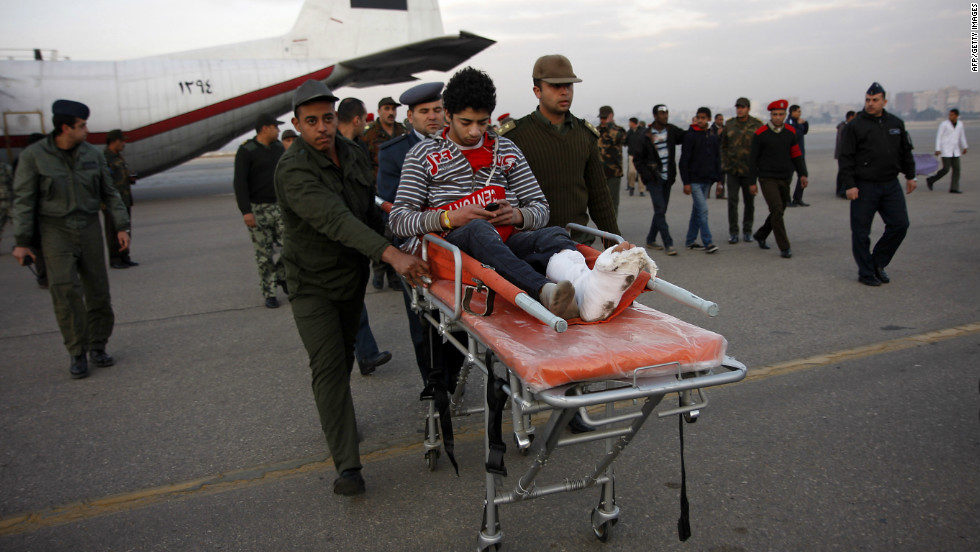 Egyptian soldiers help a wounded football Al-Ahly fan after he arrived in Cairo on a military plane.