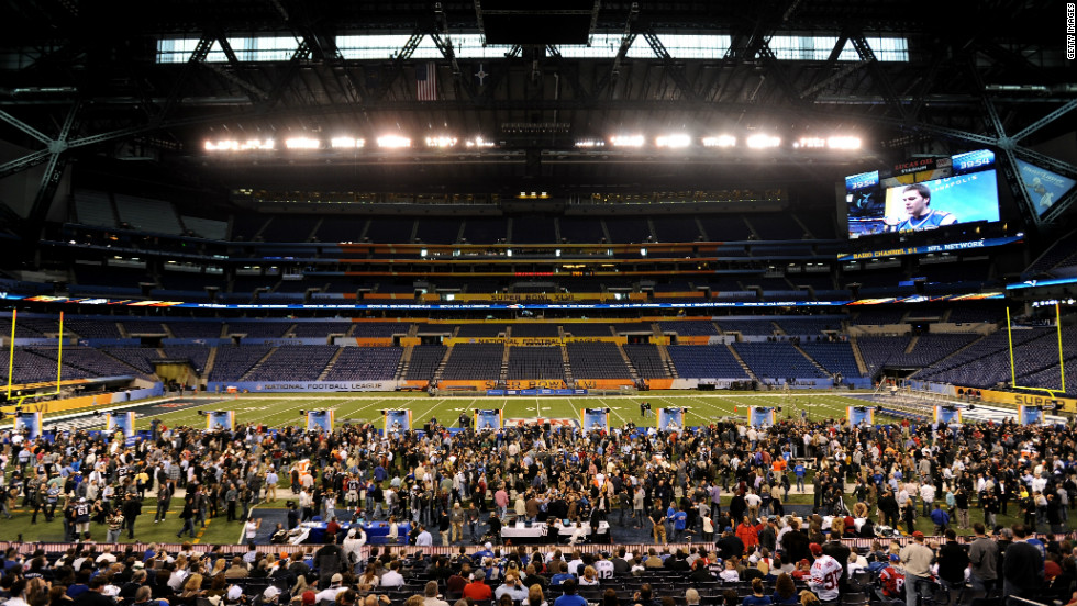 Fans gather at the Lucas Oil Stadium in Indianapolis, venue for the 46th Super Bowl, while the New England Patriots players address the media.