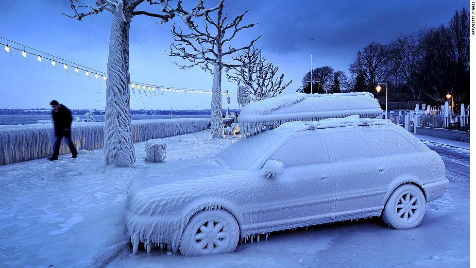 A man walks past an ice-covered car Sunday on the frozen waterside promenade at Lake Geneva in Versoix, Switzerland.