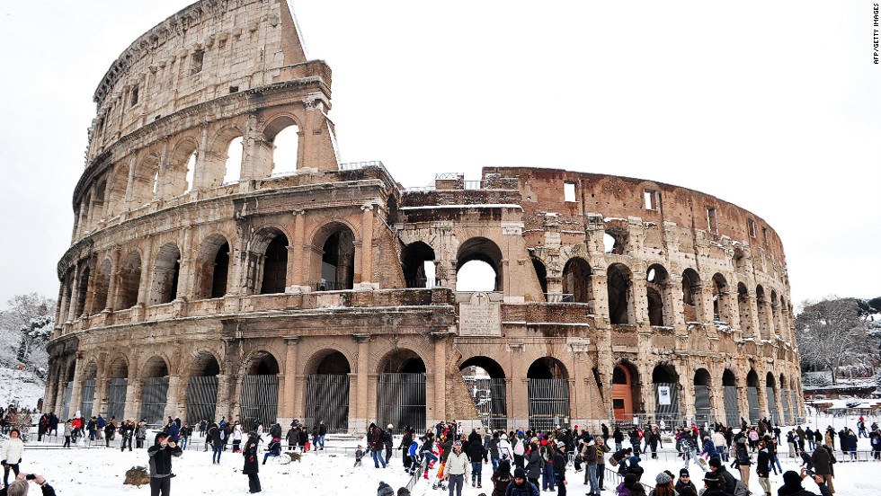 People stand in snow Saturday in front of the Colosseum in Rome.